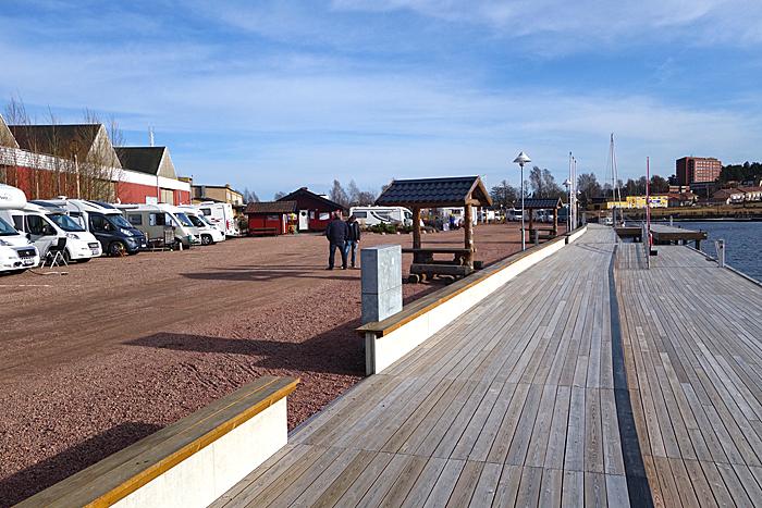 Den nyrenoverte bryggekanten foran bobilplassene egner seg godt for en ettermiddagskaffe. I bakgrunnen ser du litt av byens sentrum. Foto: Knut Randem.