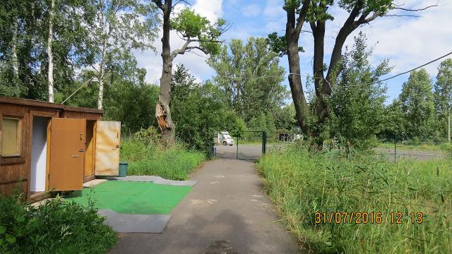 Shuvalovka Camping. Her står vi parkert på en grusplass, dusjer og toaletter i brakkene til venstre.